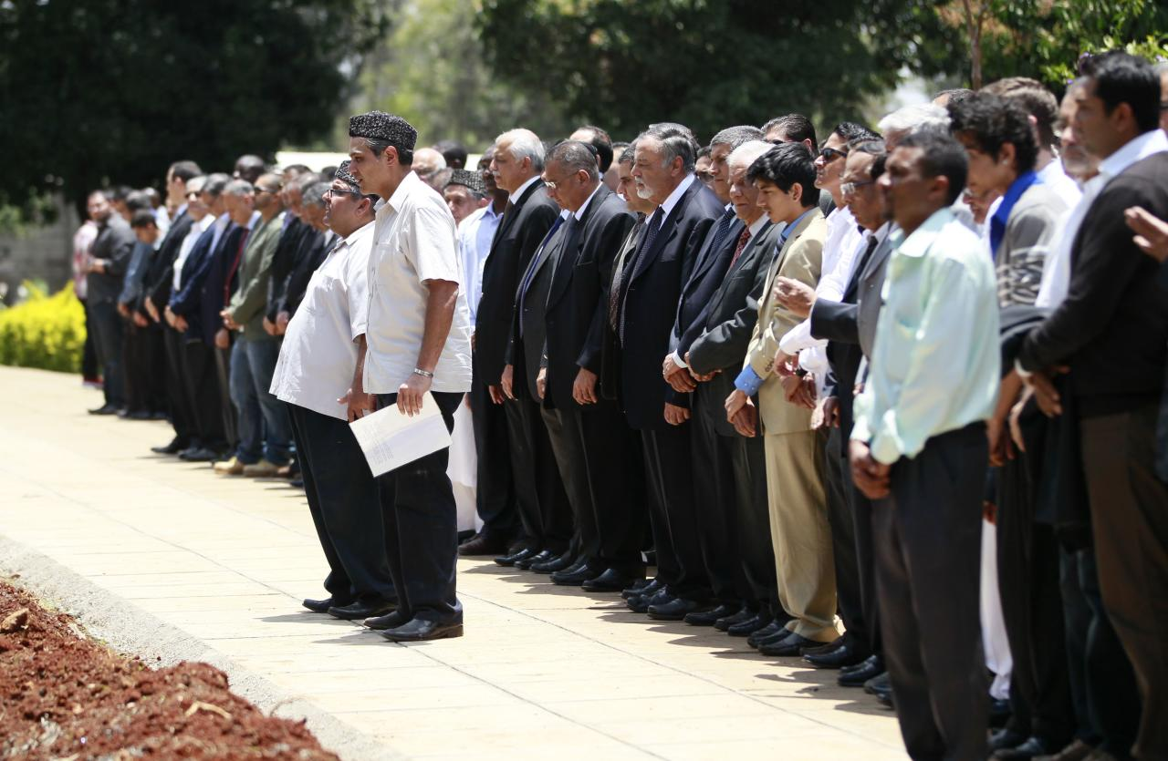 Relatives and friends perform final prayers during the burial of Kenyan journalist Ruhila Adatia Sood, who was killed in the Westgate shopping mall attack, in Kenya's capital Nairobi September 26, 2013. U.S., British and Israeli agencies are helping Kenya investigate the attack claimed by Somali Islamist militants on the Nairobi shopping mall that killed at least 72 people and destroyed part of the complex, officials said on Wednesday. REUTERS/Thomas Mukoya (KENYA - Tags: CIVIL UNREST CRIME LAW RELIGION)