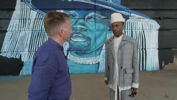 Billy Porter (with correspondent Seth Doane, left) in front of a mural of Porter, painted by artist Camerin