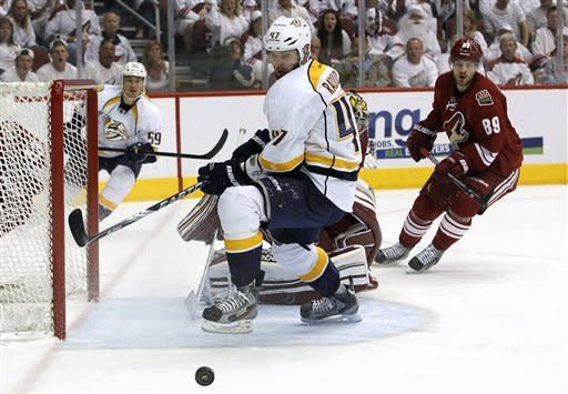 Nashville Predators' Alexander Radulov (47), of Russia, tries to get the puck in front of the goal as Phoenix Coyotes' Mikkel Boedker (89), of Denmark, and Predators' Roman Josi (59), of Switzerland, watch the second period during Game 5 in an NHL hockey Stanley Cup Western Conference semifinal playoff series Monday, May 7, 2012, in Glendale, Ariz. (AP Photo/Ross D. Franklin)