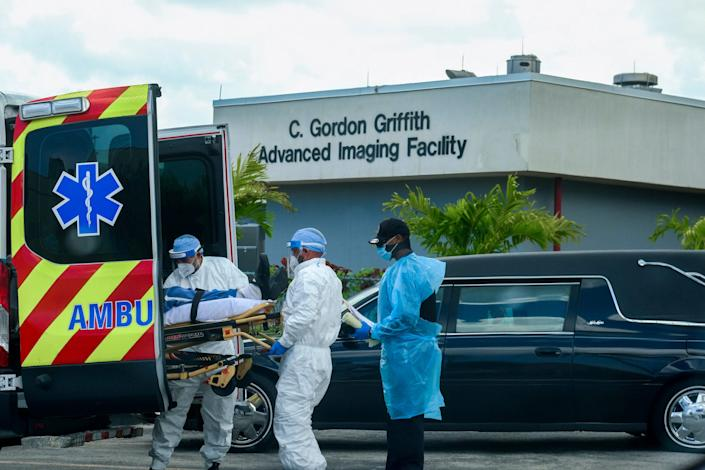 Emergency medical technicians arrive with a patient while a funeral car begins to depart at North Shore Medical Center in Miami, Florida, July 14, 2020.