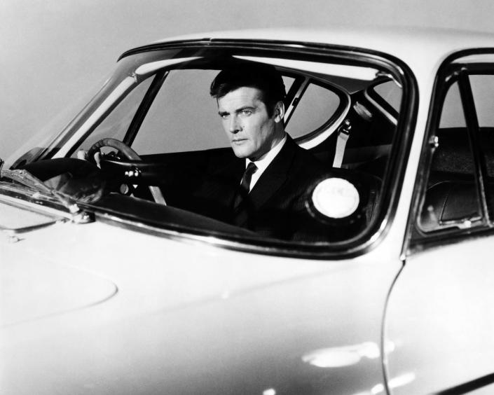 Roger Moore as Simon Templar, in a promotional portrait at the wheel of a Volvo P1800 sports car, for spy thriller TV series The Saint, circa 1965. (Credit: Silver Screen Collection/Getty Images)