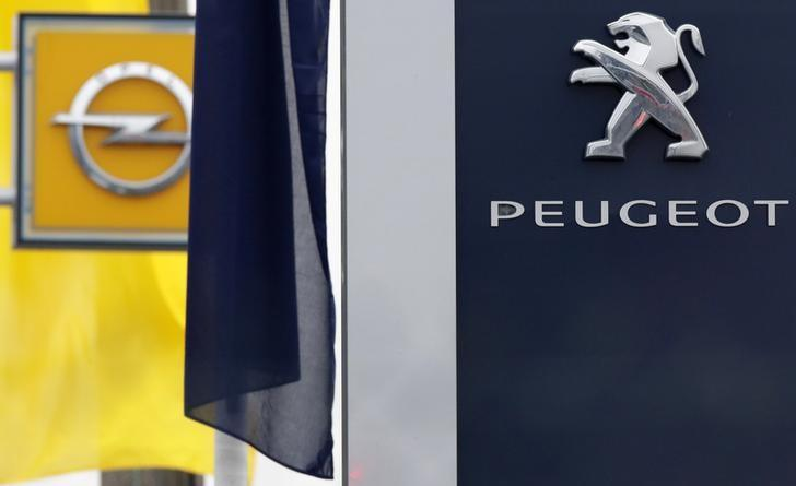The logos of French car maker Peugeot and German car maker Opel are seen at a dealership in Villepinte