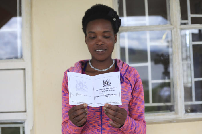 A teacher displays her vaccination certificate at the Bwama Health Centre III, at Bwama Island – Lake Bunyonyi, in Western Uganda, Wednesday April 28, 2021, after receiving her COVID-19 vaccination. The Uganda government has embarked on vaccinating people in hard to reach areas. Remote islands in Uganda have tested the efforts of health officials delivering COVID-19 vaccine doses as global efforts to access hard-to-reach areas continue. (AP Photo/Patrick Onen)