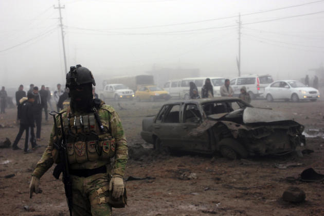 An Iraqi soldier stands guard at the site of a bomb attack in Balad Ruz, in northeastern Iraq.