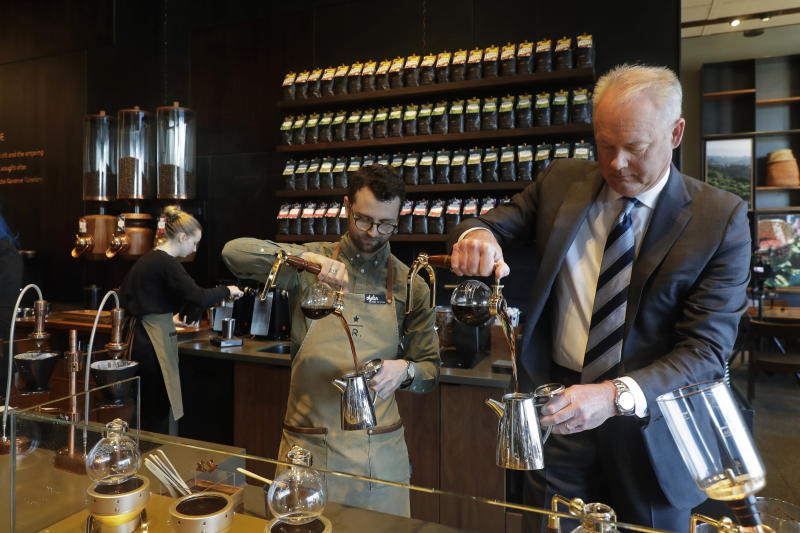 FILE- In this March 5, 2019, file photo Kevin Johnson, right, CEO of Starbucks, makes coffee using a siphon method alongside barista Dylan George, left, as Johnson visits the company's Starbucks Reserve store in the company's headquarters building in Seattle's SODO neighborhood. Starbucks Corp. reports earns on Thursday, April 25. (AP Photo/Ted S. Warren, File)