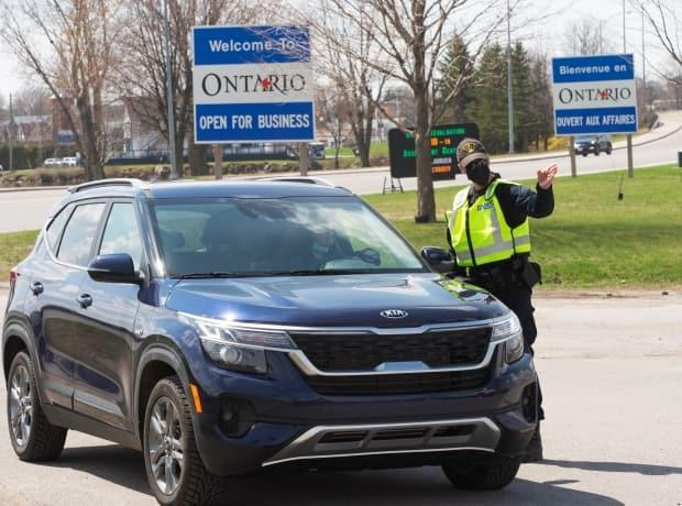 An Ontario Provincial Police officer in Hawkesbury, Ont. checks travellers entering Ontario in from Quebec when new interprovincial travel restrictions were imposed in mid-April. (Ryan Remiorz/The Canadian Press - image credit)