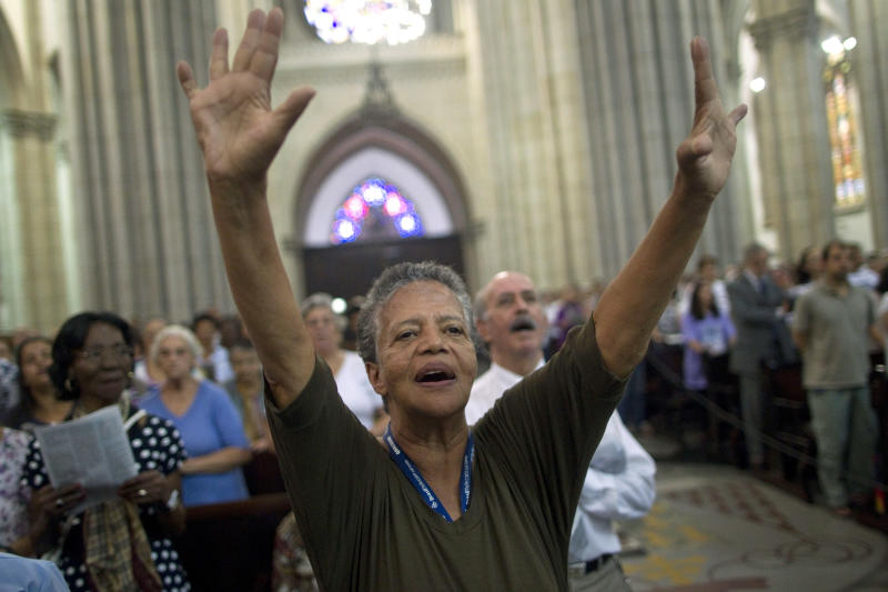 A woman holds out her arms during a Mass by Cardinal Odilo Pedro Scherer, archbishop of Sao Paulo, at the Cathedral in Sao Paulo, Brazil, Wednesday, Feb. 13, 2013. Latin America is home to the world's largest Roman Catholic population, but hopes that the next pope will come from the region appear faint, experts said Monday. Brazilian Cardinals Joao Braz de Aviz, a 65-year-old who has earned praise as head of the Vatican's office for religious congregations, and Odilo Pedro Scherer, the 63-year-old archbishop of Sao Paulo, have been mentioned as possibilities. (AP Photo/Andre Penner)