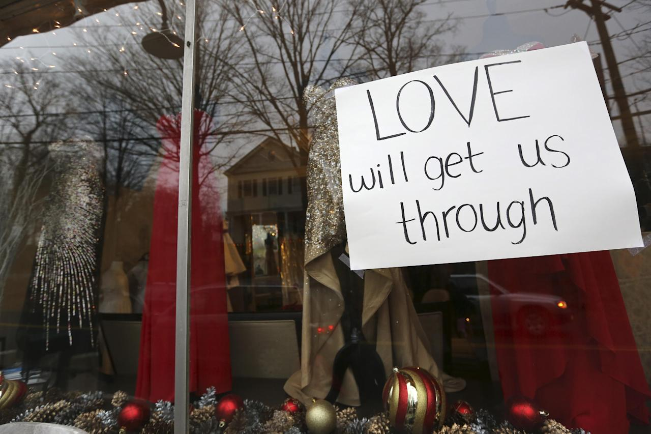 A sign hangs in the window of a clothing store Sunday, Dec. 16, 2012 in Newtown, Conn. On Friday, a gunman allegedly killed his mother at their home and then opened fire inside the Sandy Hook Elementary School, killing 26 people, including 20 children. (AP Photo/Mary Altaffer)
