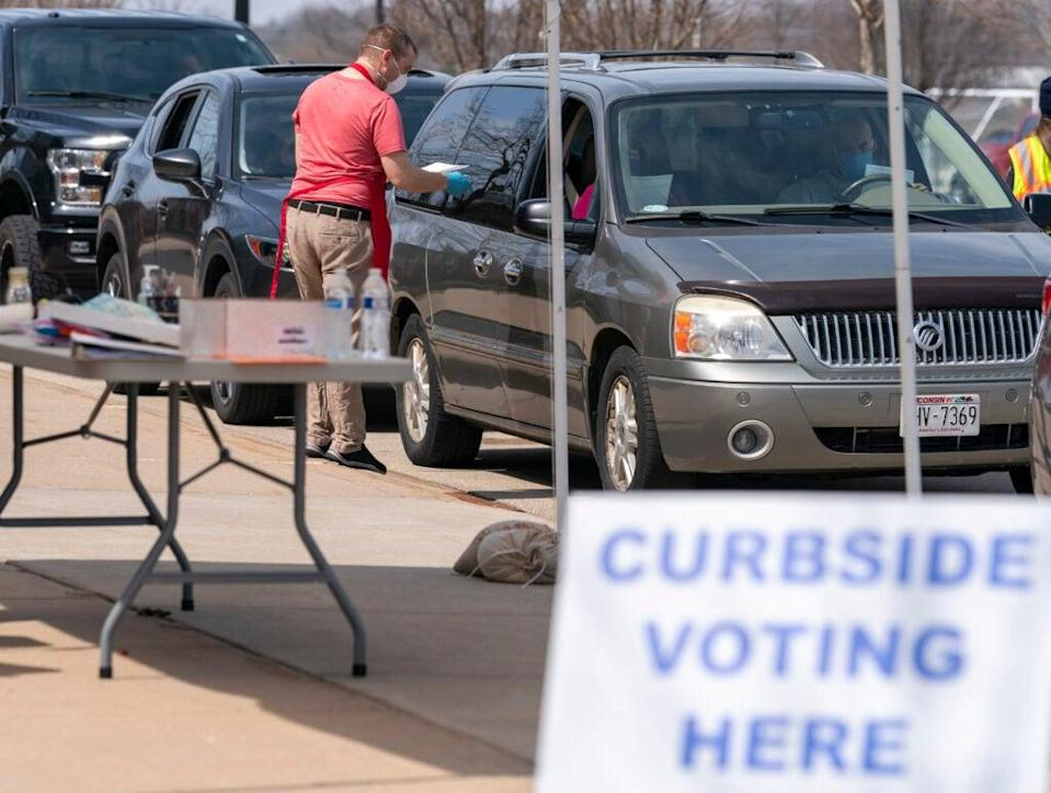 A poll worker talks to people during curbside voting on April 7, 2020 in Sun Prairie, Wisconsin. (Photo by Andy Manis/Getty Images)