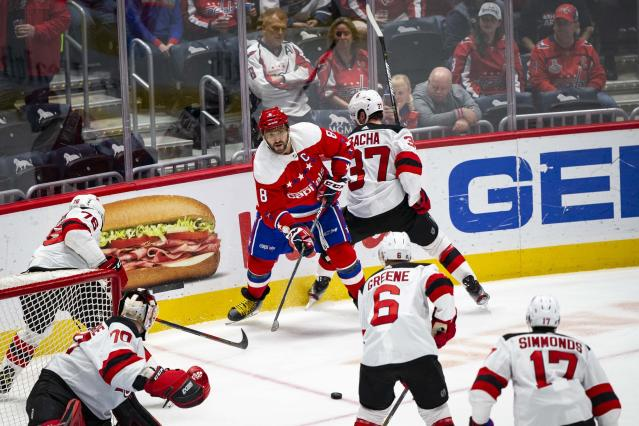 Washington Capitals left wing Alex Ovechkin (8), from Russia, passes the puck to a teammate as he is defended by New Jersey Devils center Pavel Zacha (37), from the Czech Republic, during the first period of an NHL hockey game Saturday, Jan. 11, 2020, in Washington. (AP Photo/Al Drago)