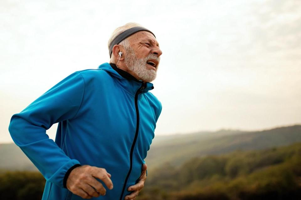 Mature athletic man getting out of breath while feeling pain during morning run in nature.
