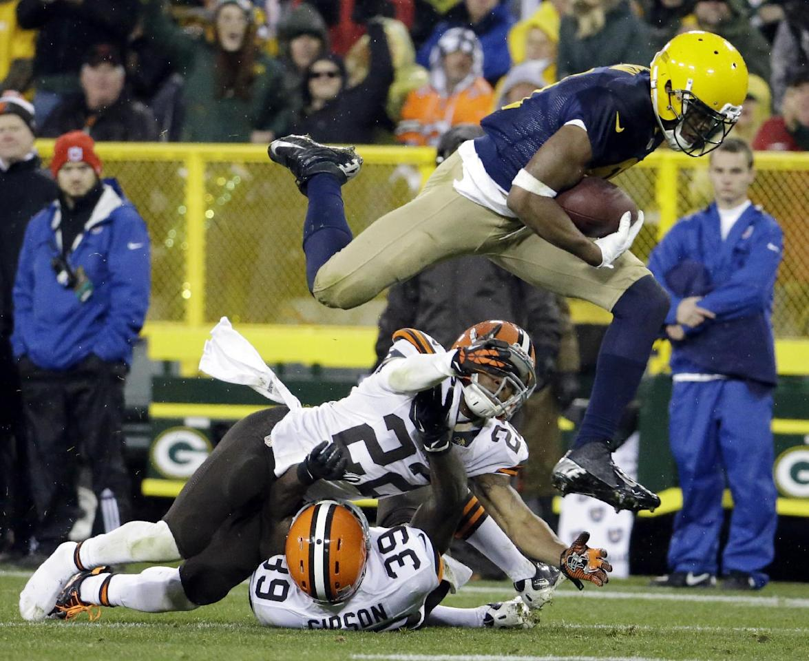 Green Bay Packers' Jarrett Boykin leaps over Cleveland Browns' Buster Skrine (22) and Tashaun Gipson (39) after a catch during the second half of an NFL football game Sunday, Oct. 20, 2013, in Green Bay, Wis. (AP Photo/Morry Gash)