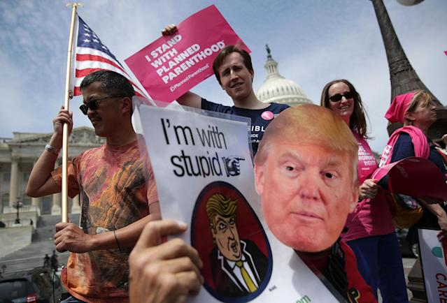 <p>Activists hold signs during a Stop 'Trumpcare' rally, May 4, 2017, in front of the Capitol in Washington, D.C. Congressional Democrats joined activists for a rally to urge the House of Representatives not to replace Obamacare, the Affordable Care Act. (Photo: Alex Wong/Getty Images) </p>