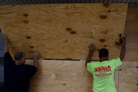 Men board up a business ahead of the arrival of Hurricane Dorian in Cocoa