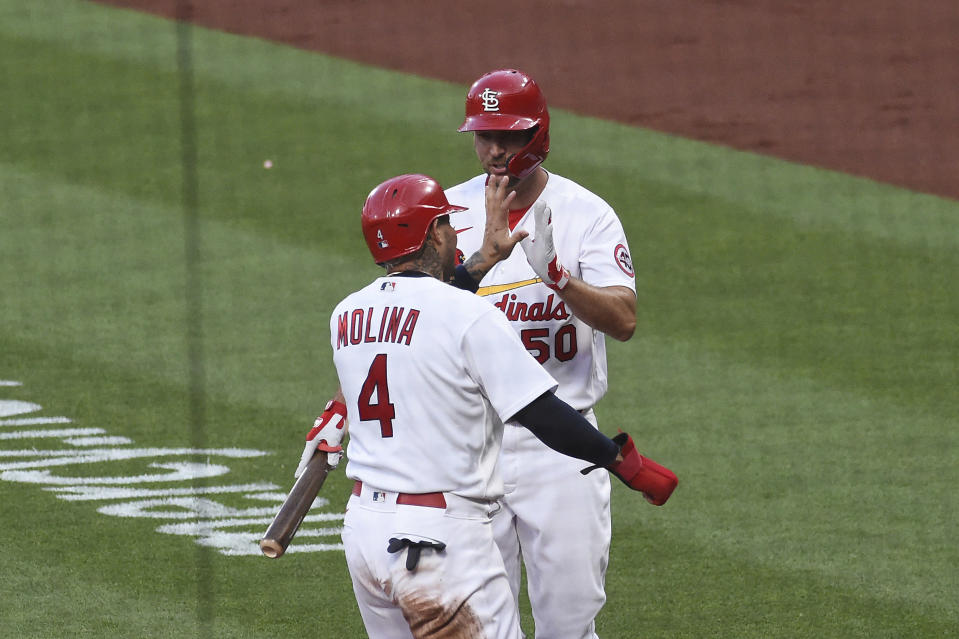 St. Louis Cardinals catcher Yadier Molina, left, is congratulated by teammates St. Louis Cardinals' Adam Wainwright after scoring a run against the Miami Marlins during the second inning of a baseball game Monday, June 14, 2021, in St. Louis. (AP Photo/Joe Puetz)
