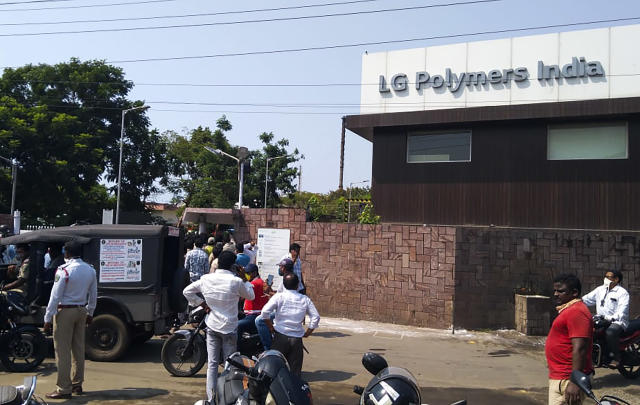Policemen stand guard as people gather in front of an LG Polymers plant following a gas leak incident in Visakhapatnam on May 7, 2020. - At least five people have been killed and several hundred hospitalised after a gas leak at a chemicals plant on the east coast of India, police said on May 7. They said that the gas had leaked out of two 5,000-tonne tanks that had been unattended due to India's coronavirus lockdown in place since late March. (Photo by - / AFP) (Photo by -/AFP via Getty Images)
