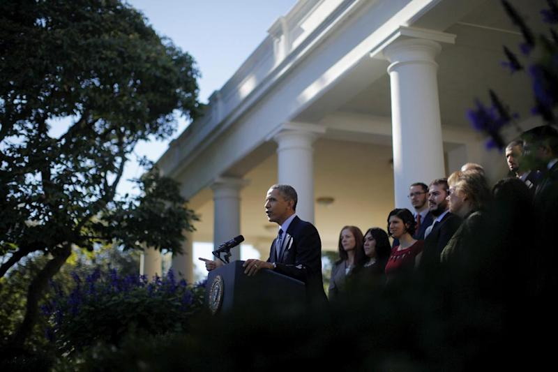 President Barack Obama, standing with supporters of his health care law, speaks in the Rose Garden of the White House in Washington, Monday, Oct. 21, 2013, on the initial rollout of the health care overhaul. Obama acknowledged that the widespread problems with his health care law's rollout are unacceptable, as the administration scrambles to fix the cascade of computer issues. (AP Photo/Charles Dharapak)