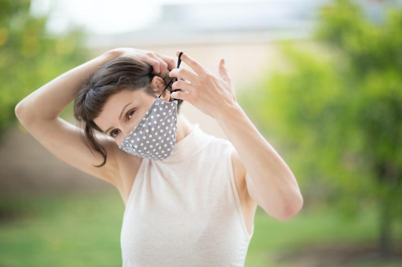 woman put on a fabric handmade mask on her face