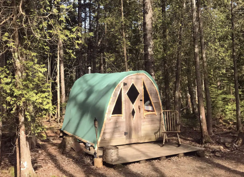 """<p><strong><a href=""""https://www.airbnb.com/rooms/16844641"""" rel=""""nofollow noopener"""" target=""""_blank"""" data-ylk=""""slk:Coyote's Den at The Howling Woods:"""" class=""""link rapid-noclick-resp"""">Coyote's Den at The Howling Woods:</a></strong><strong> Tremont, Maine</strong></p><p>This tiny wooden cabin in the middle of the woods is the closest thing you'll get to camping while still enjoying some creature comforts. It's very small, but features large windows that let in lots of light. Inside, there's enough room for a bed and a tiny heater, but not much else, and outside is a small deck with a firepit. And you're not far from civilization: this is in a village of tiny houses, so a walk to the main area will bring you to an outhouse (and past a garden and farm with animals). </p>"""