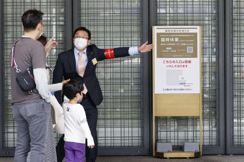 "An usher briefs visitors at an entrance of a department store which is open partially, in Tokyo Sunday, April 25, 2021. Japan's department stores, bars and theaters shuttered Sunday, as the government ""state of emergency"" over the coronavirus pandemic kicked in amid growing worries about a surge in infections. (Hiroko Harima/Kyodo News via AP)"