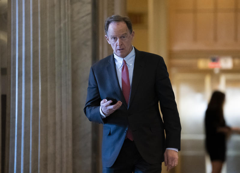 FILE - In this Feb. 3, 2020, file photo, Sen. Pat Toomey, R-Pa., walks at the Capitol in Washington. The nation's fiercest fiscal conservatives are largely embracing the massive economic rescue package moving through Congress. In many cases, those conservatives who support the $2 trillion coronavirus spending bill are the very same who raged against the $800 billion economic stimulus package backed by the Obama administration after the 2008 financial crisis. (AP Photo/J. Scott Applewhite, File)