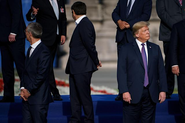 <p>President Trump, right, waits with NATO Secretary-General Jens Stoltenberg before they pose ahead of a working dinner at the Parc du Cinquantenaire in Brussels on July 11, 2018, during the NATO summit. (Photo: Brendan Smialowski/AFP/Getty Images) </p>