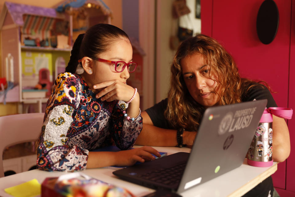 LOS ANGELES, CA - SEPTEMBER 17:      9-year-old Priscilla Guerrero uses a laptop computer for her 4th grade Los Angeles Unified School District online class in her room as mom Sofia Quezada assists her and 13-year-old sister Paulette Guerrero during remote learning lessons at home on September 17, 2020.  Boyle Heights on Thursday, Sept. 17, 2020 in Los Angeles, CA. (Al Seib / Los Angeles Times