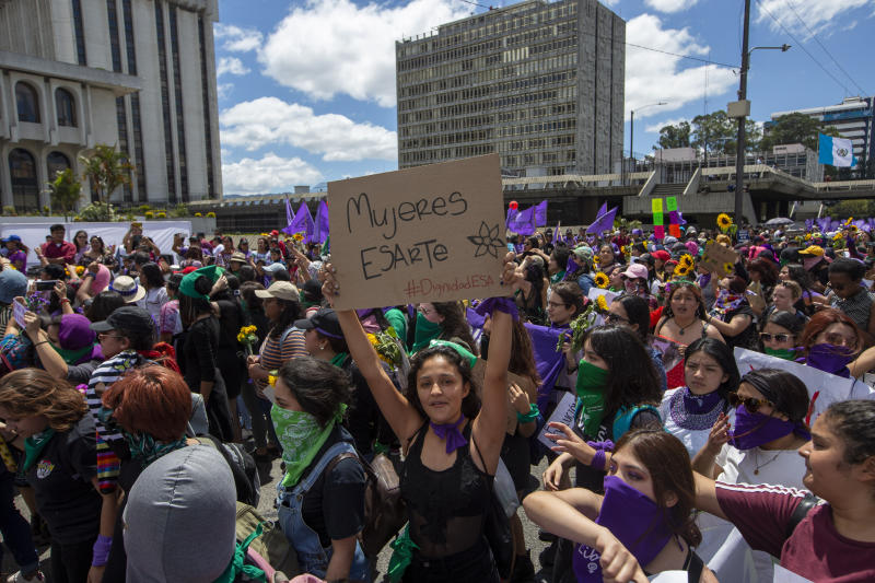 Women march in front of the Supreme Court during International Women's Day in Guatemala City, Sunday, March 8, 2020. (AP Photo/Moises Castillo)