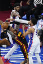 Atlanta Hawks' John Collins, left, tries to get a shot past Philadelphia 76ers' Joel Embiid, center, and Tobias Harris during the first half of Game 7 in a second-round NBA basketball playoff series, Sunday, June 20, 2021, in Philadelphia. (AP Photo/Matt Slocum)