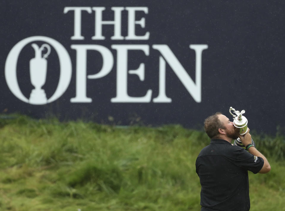 FILE - In this Sunday, July 21, 2019 file photo, Ireland's Shane Lowry holds and kisses the Claret Jug trophy on the 18th green as he poses for the crowd and media after winning the British Open Golf Championships at Royal Portrush in Northern Ireland. The British Open is heading back to Royal Portrush. The R&A says the world's oldest major championship will return to the Northern Irish venue in 2025 after a successful staging of the British Open there in 2019 when Irish player Shane Lowry won by six shots. That marked the first time Royal Portrush had hosted the event since 1951. (AP Photo/Peter Morrison, File)
