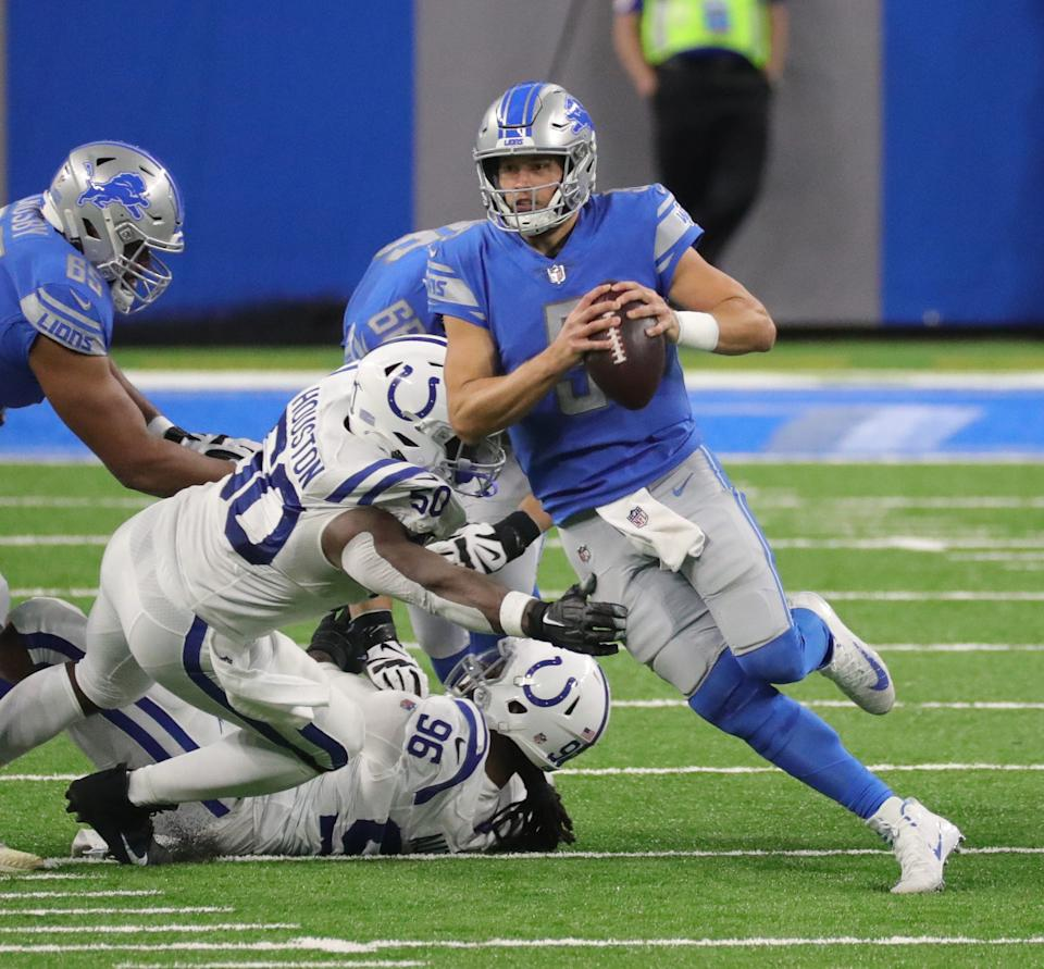 Detroit Lions quarterback Matthew Stafford runs past Indianapolis Colts defenders during the second half at Ford Field, Sunday, Nov. 1, 2020.