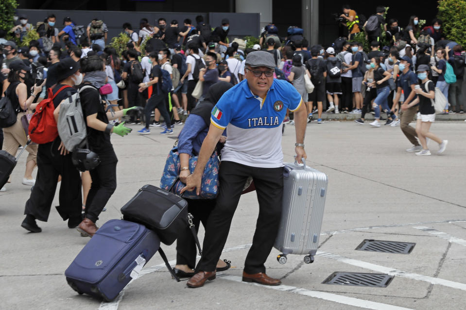 Passengers and pro-democracy protestors run as riot police arrive outside the airport in Hong Kong, Sunday, Sept. 1, 2019. The operator of the express train to Hong Kong's airport has suspended service as pro-democracy protesters gathered there following a day of violent clashes with police. Protesters gathered at the airport after online calls to disrupt travel. (AP Photo/Kin Cheung)