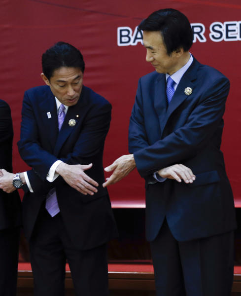 Japanese Foreign Minister Fumio Kishida, left, and his South Korean counterpart Yun Byung-se prepare to join their hands for a group photo at the 46th ASEAN Foreign Ministers' Plus Three Meeting in Bandar Seri Begawan, Brunei, Sunday, June 30, 2013. (AP Photo/Vincent Thian)