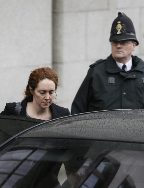 Rebekah Brooks, the former chief of News Corp.'s British newspapers, is watched by a policeman as she leaves a hearing at the Old Bailey court in the City of London, Friday, March 8, 2013, in London. Brooks is appearing in court to face charges over alleged conspiracy to bribe a public official to obtain information. (AP Photo/Kirsty Wigglesworth)