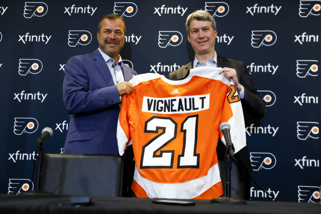 FILE - In this April 18, 2019, file photo, Alain Vigneault, left, newly hired Philadelphia Flyers head coach, and general manager Chuck Fletcher pose for a photograph after an introductory press conference at the Flyer's practice facility in Voorhees, N.J. When NHL officials approached the Philadelphia Flyers about appearing on their latest behind-the-scenes show, they faced almost no resistance. There werent many reservations, general manager Chuck Fletcher said. There really aren't any negatives as far as I'm concerned. The Flyers will be featured on NHL Networks second season of Behind the Glass that gives a peek behind the curtain to training camp, exhibition games and the regular-season opener in Europe. (AP Photo/Matt Slocum, File)