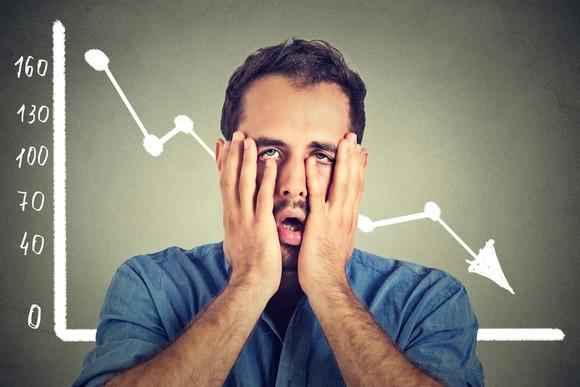 A man holding his face in front of a falling stock chart.