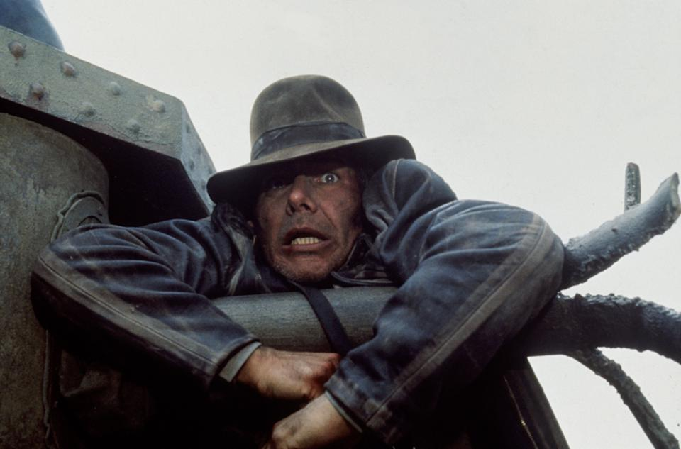 American actor Harrison Ford as the eponymous archaeologist in a scene from the film 'Indiana Jones and the Last Crusade', 1989. Here he hangs from the gun of a German tank during a chase scene.  (Photo by Murray Close/Getty Images)