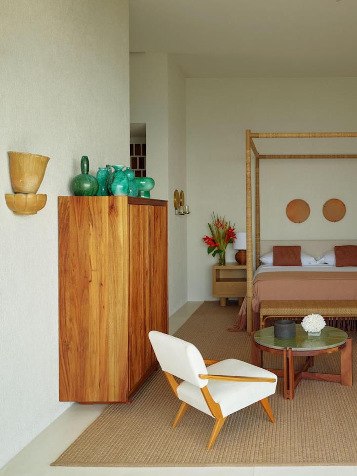 A Gio Ponti Armchair and a Sika-Design Rattan bench mingle with pieces by Laplace in a guest bedroom.