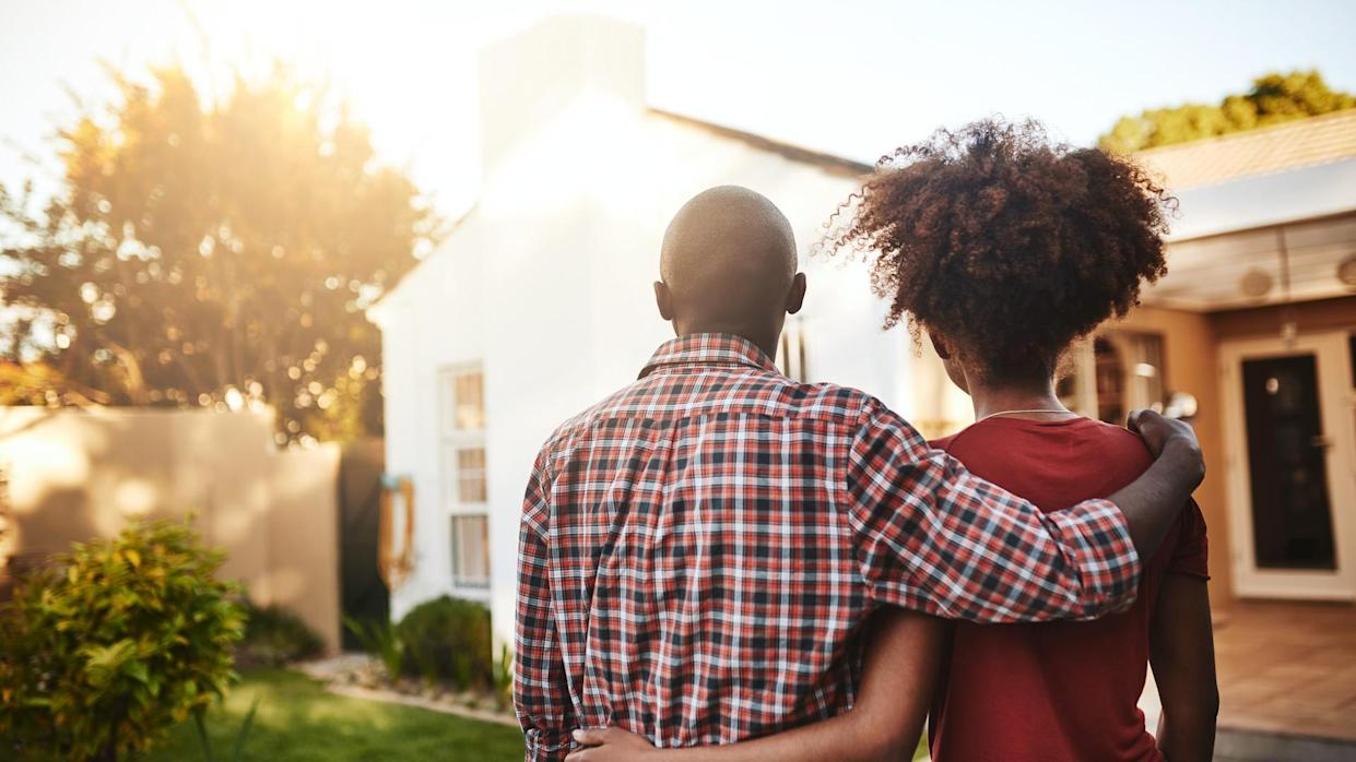 Rear view shot of a young couple admiring their new house outside.