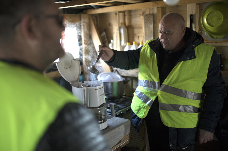 A yellow vest protester prepares coffee for fellow protesters in the l'Étoile yellow vests camp after a demonstration at the l'Étoile road toll lanes marking the one year anniversary of the yellow vest movement near Marseille, southern France, Saturday, Nov. 17, 2019.  Some protests have clashed with police as yellow vest protesters are marking a year of protests, seeking what they see as economic justice for the French people with changes in government policies. (AP Photo/Daniel Cole)