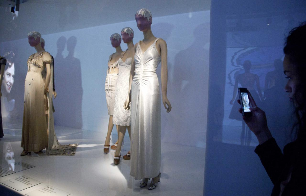 """A woman photographs a display of fashions by Elsa Schiaparelli and Miuccia Prada at the Metropolitan Museum of Art, Monday, May 7, 2012 in New York. The show """"Schiaparelli and Prada, Impossible Conversations,"""" opens May 10 and continues through Aug. 19. (AP Photo/Mark Lennihan)"""