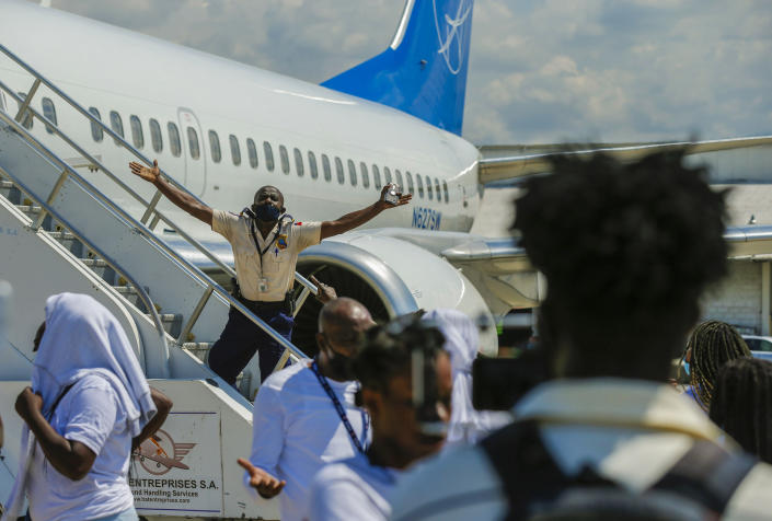A police officer tries to block Haitians deported from the United States from boarding the same plane they were deported on, in an attempt to return to the United States, on the tarmac of the Toussaint Louverture airport, in Port-au-Prince, Haiti, Tuesday, Sept. 21, 2021 (AP Photo/Joseph Odelyn)