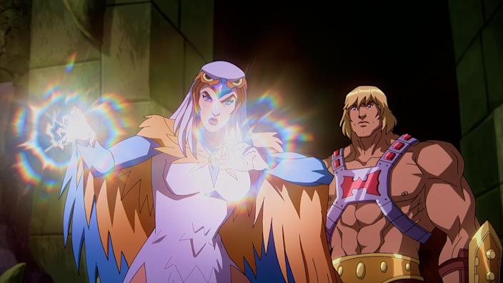 """In a CG animated still from Masters of the Universe: Revelation, He-Man (right) stands behind Sorceress (left) in a stone room lit only by the light coming from SorceressesÕ hands. Sorceress has her palms outstretched in front of her and wears a white dress, a falcon-like hood over head and orange and blue wings. He-Man wears a silver chest plate with a red """"H"""" in the center, a golden armored belt and wrist plates."""