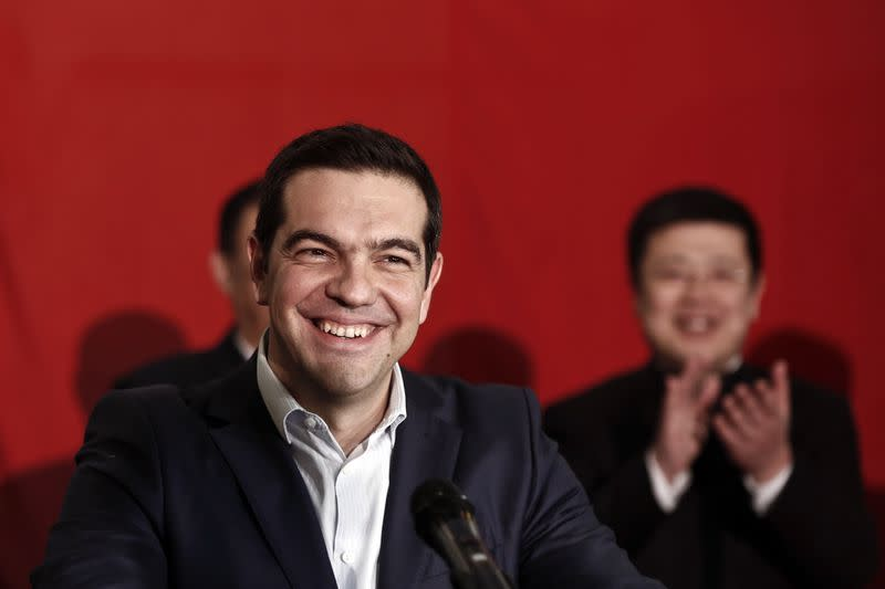Greek PM Tsipras smiles during his speech aboard the Chinese frigate Changbaishan at the port of Piraeus, near Athens