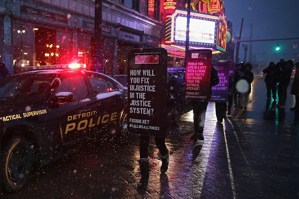 DETROIT, MI - MARCH 03: Demonstrators march with signs made to look like law enforcement riot shields while protesting against police violence outside the historic Fox Theatre before the GOP presidential debate March 3, 2016 in Detroit, Michigan. Voters in Michigan will go to the polls March 8 for the stateÕs primary. (Photo by Chip Somodevilla/Getty Images)