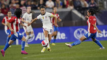 U.S. forward Carli Lloyd, center, moves the ball past Paraguay midfielders Fanny Godoy, left, and Cynthia Ayala, right, during the second half of an international friendly soccer match Thursday, Sept. 16, 2021, in Cleveland. USA won 9-0. (AP Photo/Tony Dejak)