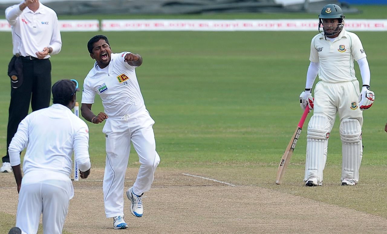 Sri Lankan cricketer Rangana Herath (C) celebrates after he dismissed Bangladeshi cricketer Mominul Haque during the fourth day of the second Test match between Sri Lanka and Bangladesh at the R. Premadasa Cricket Stadium in Colombo on March 19, 2013.   AFP PHOTO/ LAKRUWAN WANNIARACHCHI