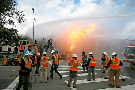 FILE PHOTO: PG&E officials are seen as firefighters battle a fire following an explosion at Geary boulevard and Parker Avenue in San Francisco
