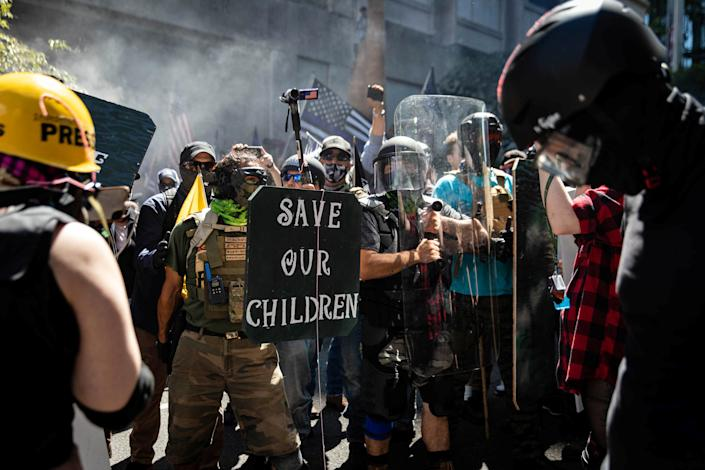 """People, including one person holding a """"Save Our Children"""" sign, at a protest in front of a Blue Lives Matter flag"""