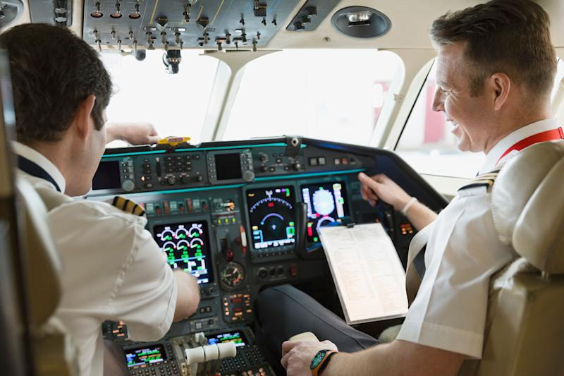 Male pilot and co-pilot checking instrument panel in airplane cockpit. Getty Images